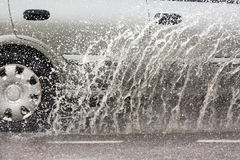 Car driving through a puddle on a flooded road with water and splashes caused by heavy rain. Stock Photography