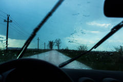 Car driving in rain. Dark clouds and road ahead royalty free stock photo