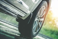 Car Driving in the Rain. Modern Rain Summer Season Tires on the Wet Pavement. Closeup Aquaplaning Photo royalty free stock photography