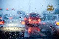 Car driving in rain and storm abstract background. Car windshield with rain drops during storm and blurred stoplights Stock Photography