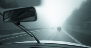 Car driving in the rainy weather. Driving car in the rainy weather on slippery highway. View through vehicle windshield of moving car on highway. Car with active royalty free stock photo