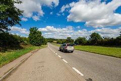 Car driving on the road. Car driving along the straight country-road at summer time royalty free stock photo