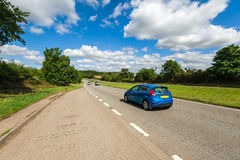 Car driving on the road. Blue car driving along the straight country-road at summer time stock images