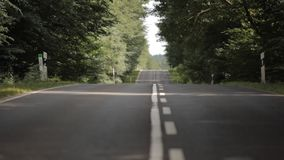 Car driving on road. Car driving down road through a forest in Germany stock video