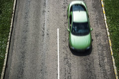 Car driving on road in green neighbourhood Stock Photo