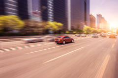 Car driving on road at sunset, motion blur Stock Images