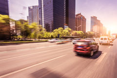 Car driving on road at sunset, motion blur Stock Photos