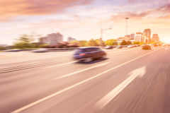 Car driving on road at sunset, motion blur Royalty Free Stock Photography