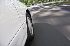 Car driving on rural road. Side view of car driving on rural road with trees in background; slow motion blur effect Stock Photo
