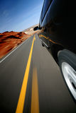 Car driving on rural road with motion blur royalty free stock photography