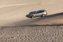 Car driving through sand dune Stock Image