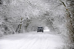 Car driving through snow covered country lane Stock Photos