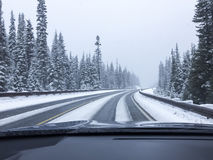 Car driving on snow-covered snowy mountain road in winter snow. Driver`s point of view viewpoint looking through windshield. Stock Photos
