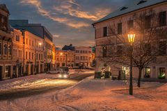 Car driving in snowfall in magical old street with lanterns royalty free stock images