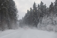 Car driving through a snowy forest Stock Photo