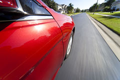Car Driving at Speed on Suburban Street Royalty Free Stock Image