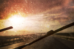 Car driving at stormy weather with glare. Dangerous blurry car driving in the stormy weather with sun and slippery road. Car windshield wipers on in the rainy stock image