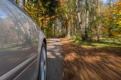 Car driving on a street in autumn Royalty Free Stock Photography