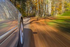 Car driving on a street in autumn Stock Images