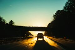 Car driving into the sunset Stock Images