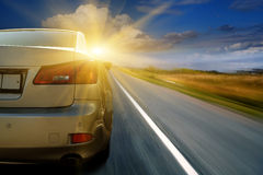 Car driving towards sunshine stock image