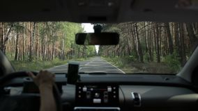 Car driving on two lane road in the forest stock video footage