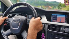 Car driving using navigation. AGAPIA, ROMANIA - July 24, 2018: Driver`s hand on the steering wheel and following car navigation system stock photo