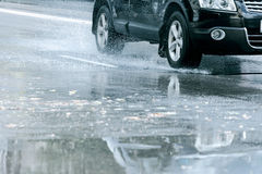 Car driving through water puddle and reflecting in it Royalty Free Stock Photo