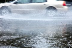 Car driving on wet road on fast speed creating water splashes. Car driving on city road on fast speed creating water splashes Royalty Free Stock Images
