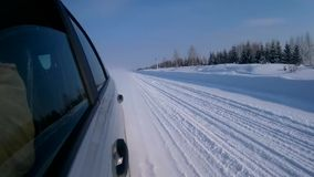 Car is driving on a winter road in the cold sunny day. View backward stock footage