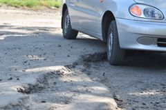 The car drove into the pit on the road. Wheel closeup. Pothole royalty free stock images
