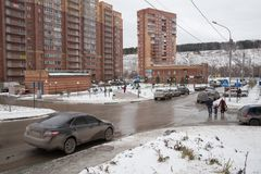 The car drove up to the intersection with a pedestrian crossing in the microdistrict with brick apartment buildings in the winter. Novosibirsk, Novosibirsk stock photography