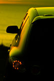Car at dusk. A modern car parked near the ocean (sea) at dusk. The sun reflected in its side window Stock Images