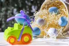 Easter Car with blue egg on background of basket with eggs. Car Easter egg on the background of baskets with hay and colored eggs stock photos
