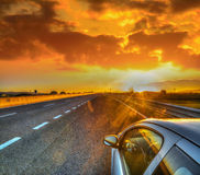 Car on the edge of the road under a scenic sky at sunset Stock Photos