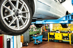 Car on an elevator or hoist in a workshop. Car on an elevator or hoist in a repair workshop or garage with focus to the rear wheel and a view of the tools in the stock photography