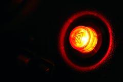 Car emergency button at night - as danger symbol. Burning car emergency button at night on plastic panel - as danger symbol. Closeup shot Stock Images