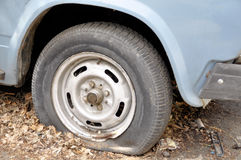 A car with an emergency standing for a long time in the fall unattended with a flat tire stock image