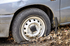 A car with an emergency standing for a long time in the fall unattended with a wheel Stock Photos
