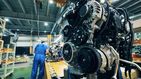 Car engine at a car manufacturing plant. Close up. Factory facility interior, industrial equipment.