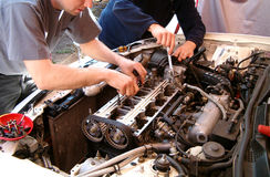 Car engine mechanic. Couple of mechanics repairing an engine of a race car. Internals of a Baltic Championships race car engine bay Royalty Free Stock Photos