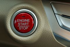 Car engine start button. Car engine start-stop button. Red button on beige leather background Royalty Free Stock Photo