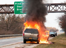 Car engulfed in flames. A brown car on fire on the side of the highway on long island, NY Stock Photos
