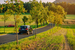 Car europe travel. Car travel on Europe road with field and trees at warm sunset light Stock Images