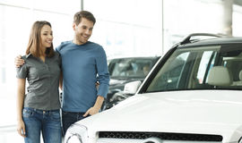 This car is exactly what we want. Beautiful young couple standing at the car dealership and making their decision