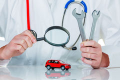 Car is examined by doctor. A model of a car is examined by a doctor. photo icon for workshop, service and car buying royalty free stock image