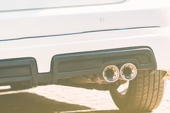 Car exhaust pipe. Close up of exhaust pipe of a white car - Color filter style pictures Stock Photography