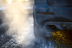 Car exhaust pipe, which comes out strongly exhaust gases in Finland. It is winter and the car is very dirty Royalty Free Stock Image