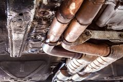 Car exhaust pipes underneath the vehicle. Car exhaust pipes during car inspection closeup royalty free stock photo