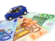 Car expenses. Blue car over euro notes and coins. Shallow DOF Royalty Free Stock Photography
